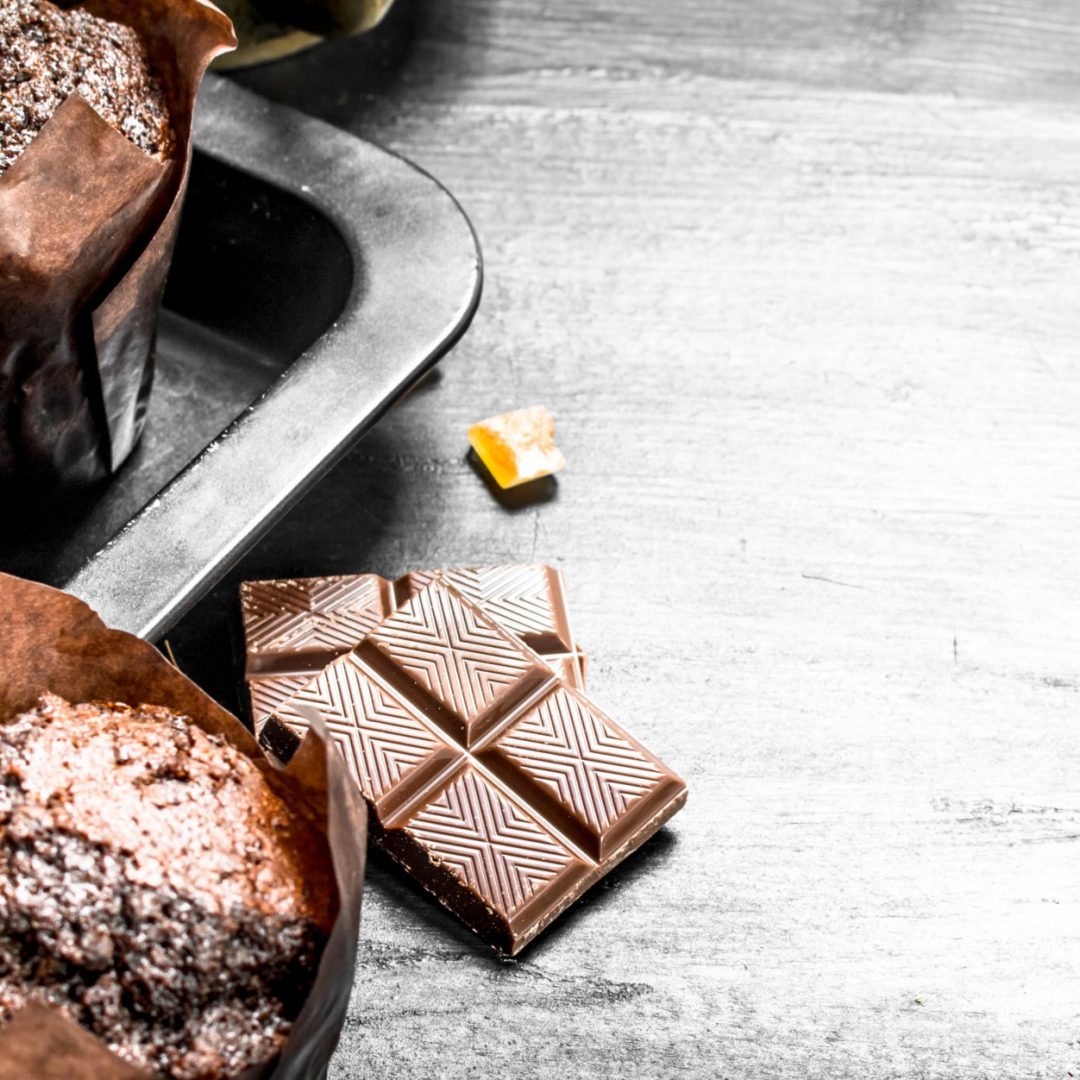 Chocolate muffins with chunks of chocolate. On the black chalkboard.